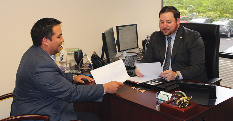 Federal Focus—Chris Turley of First Virginia Community Bank (right) talks with a government-contractor client, Gino Degregori of Bravo Consulting Group LLC in Reston, Va.