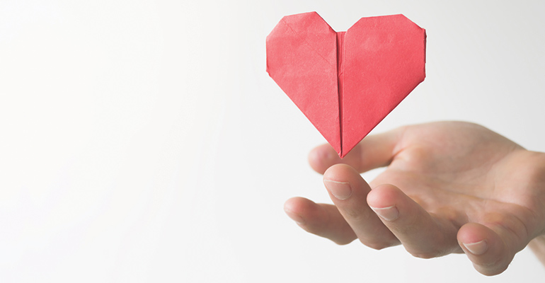 A hand holding a paper heart
