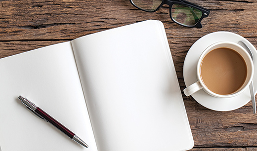 Notepad pen glasses and a cup of coffee on a table