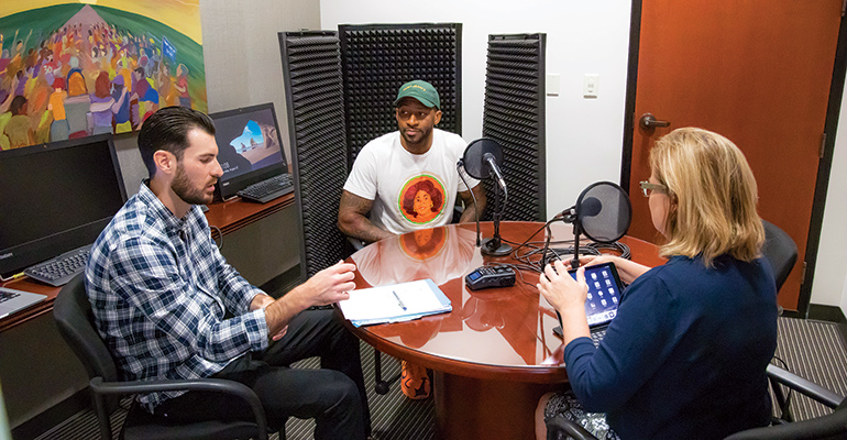 Three podcast attendees around a table