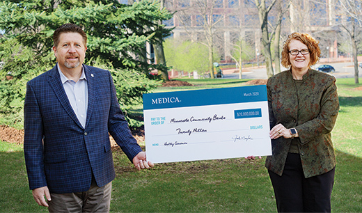 Mary Quist presents Jim Amundson with an honorary $20 million check