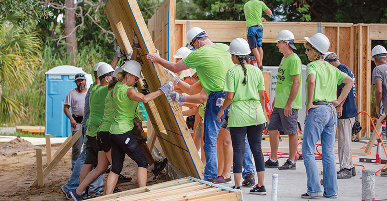 group of people working on a habitat for humanity site