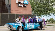 Employees of Bell Bank sitting on a car