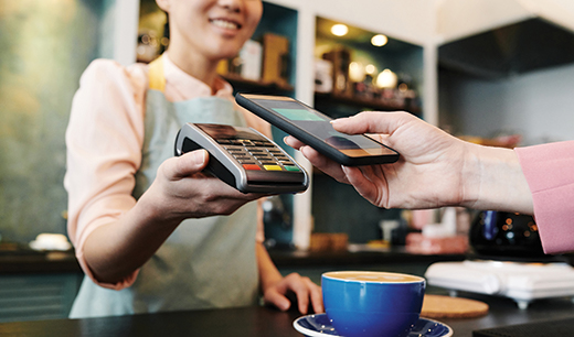 woman paying for coffee with phone