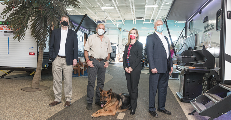 President and CEO Joanne Rau of Chelsea State Bank poses with customer Jerry Bridges, his dog, and the community bank's Mark Burmis, and Steve Saules